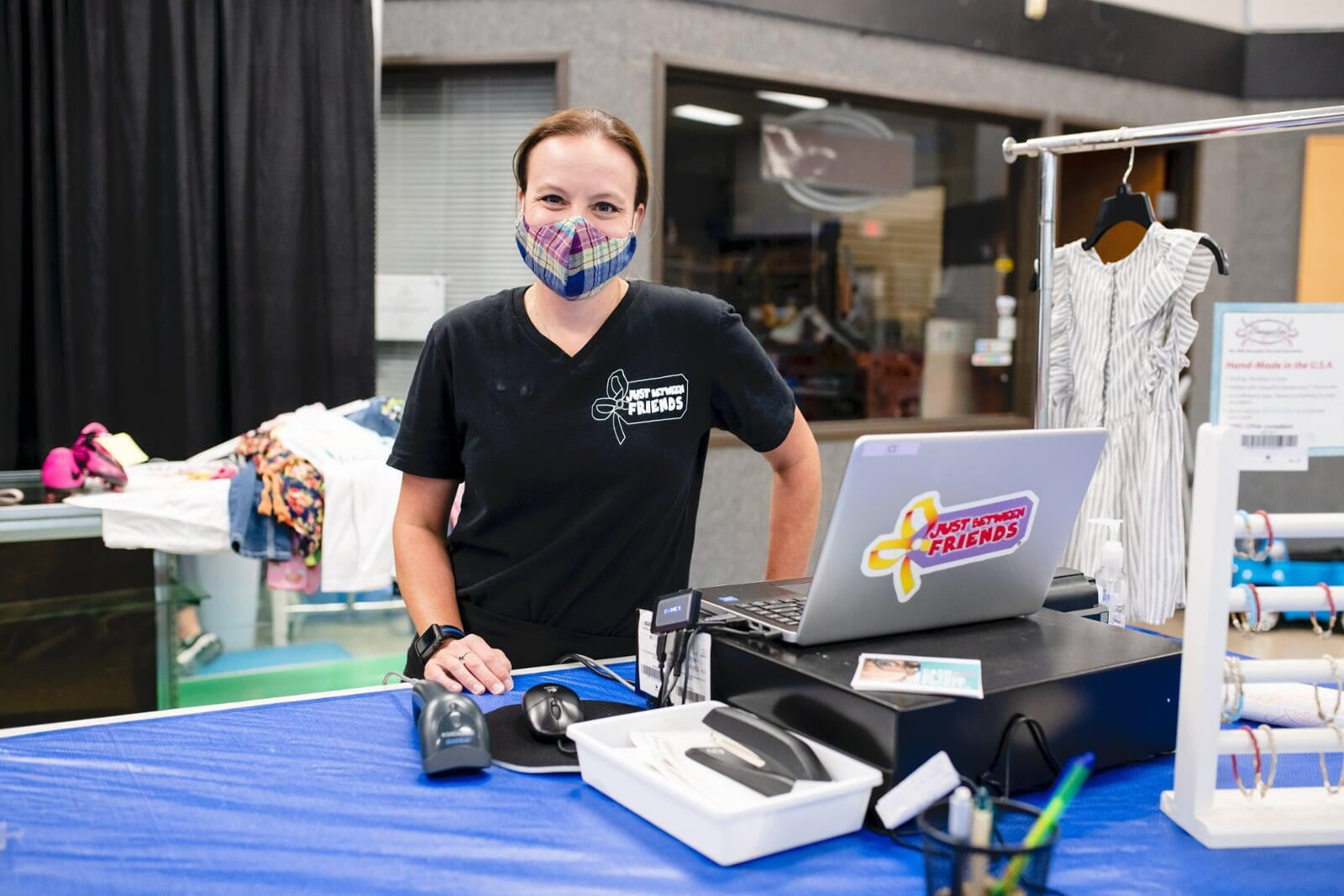 A cashier smiles behind her mask as she gets ready to check out the next happy JBF customer.