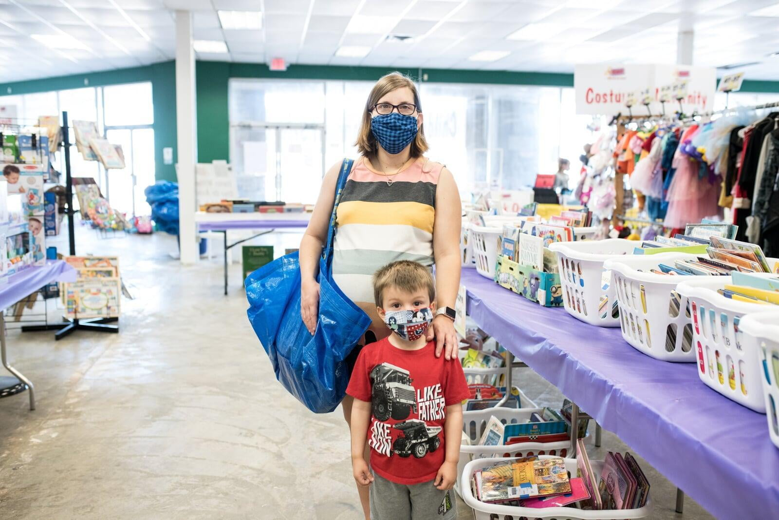 A mom and her four-year-old son stand with their masks and shopping bag in front of baskets of books and costumes.
