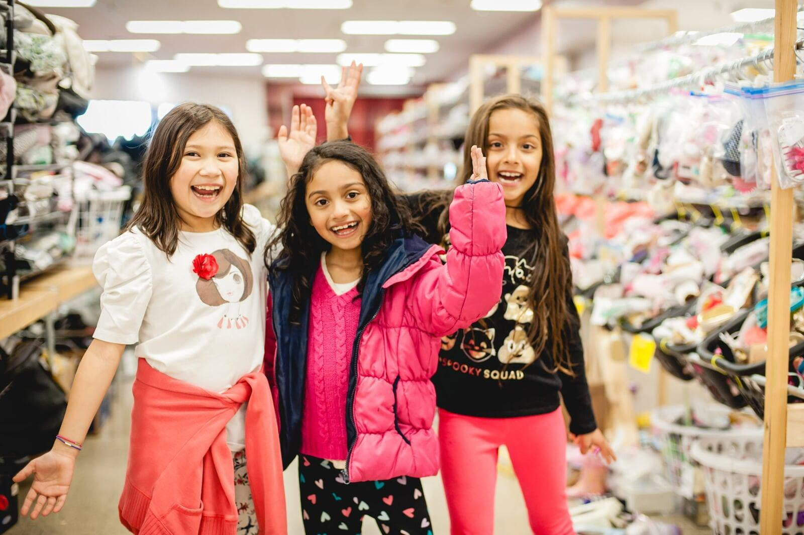 Three young girls are excited to shop together in the toy section of their local JBF sale.
